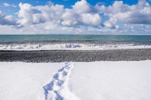 orme sulla spiaggia con la neve foto