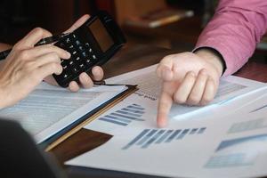 discussioni di ricerca economica, team aziendale che analizza tabelle di reddito e grafici per pianificare il concetto di marketing con l'utilizzo della calcolatrice per l'analisi. foto