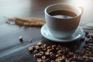 tazza di caffè sulla scrivania in legno presso la caffetteria - effetto vintage. foto