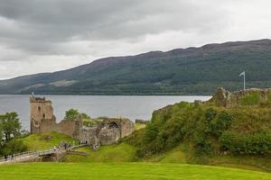 Le persone che si godono la visita al castello di Urquhart sulle rive di Loch Ness in Scozia foto