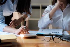 Close up di imprenditrice utilizzando la calcolatrice per matematica e finanza mentre si discute con il cliente sulla scrivania in legno. foto