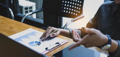 Close up imprenditrice utilizzando una calcolatrice per fare matematica per la finanza su una scrivania di legno in un ufficio con un background lavorativo aziendale, fiscale, contabilità, statistiche e concetto di ricerca analitica foto