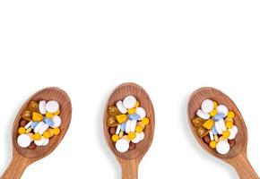 pillole medicinali in cucchiai di legno su sfondo bianco con spazio di copia foto