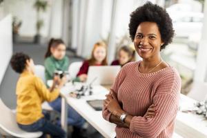 insegnante di scienze femminile afroamericana con un gruppo di bambini che programmano giocattoli elettrici e robot in aula di robotica foto