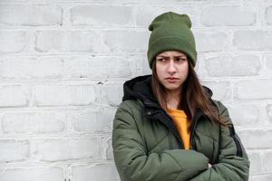 ritratto di una bella ragazza triste con un maglione giallo e un cappello cachi foto