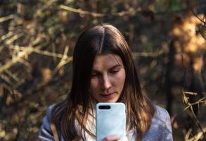 ragazza in un cappotto grigio prende un selfie nella foresta foto