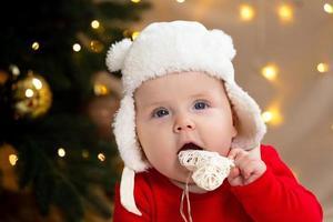 bambino di Natale guardando la telecamera e tenendo una ghirlanda con i cuori foto