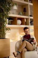 bel giovane in abiti casual e con gli occhiali da vista leggendo un libro foto
