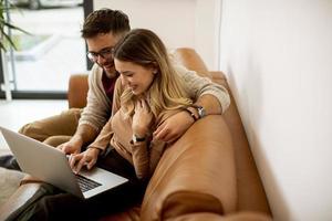 giovane coppia utilizzando laptop insieme mentre è seduto sul divano di casa foto
