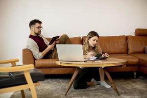 giovane donna e giovane uomo utilizzando laptop mentre è seduto dal divano di casa foto