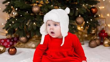 una bambina carina in un vestito rosso e un cappello bianco esprime emozioni foto