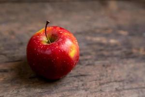 una mela con gocce d'acqua posta sul tavolo di legno foto