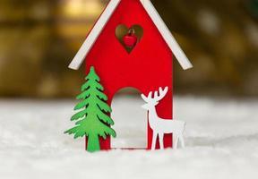 cervo di casa di legno del giocattolo di Natale e albero su una coperta bianca che imita la neve foto