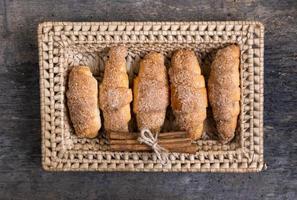 i croissant giacciono in un cesto di vimini con cannella foto