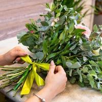 donna fioraio che fa bouquet di fiori presso il negozio foto