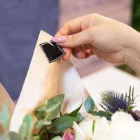 fioraio donna che fa di un bouquet di fiori e mettendo adesivo logo posto foto