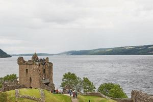 persone al castello di urquhart sulle rive di loch ness, scozia foto