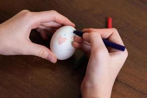 primo piano delle mani di donna colorare un uovo di Pasqua foto