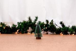 albero di natale in miniatura sullo sfondo sfocato con luci di Natale foto