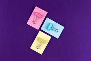 blocco note con set di graffette colorate su sfondo viola foto
