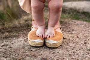le gambe di un bambino stanno sui piedi della madre foto