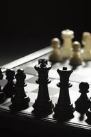 pezzi degli scacchi neri contro squadra bianca foto