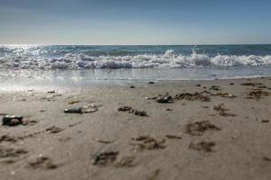 surf sulla spiaggia in controluce con conchiglie di sabbia onde e meduse foto