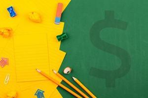 illustrazione di cancelleria scolastica con segno di dollaro e carta arancione foto