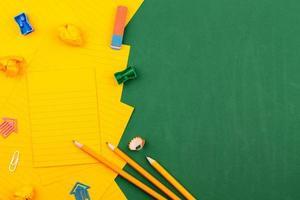 cancelleria scolastica e foglio di carta arancione si trovano sul consiglio scolastico verde foto