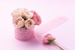 un bouquet di bellissime rose si trova in un piccolo secchio su un nastro di pizzo su uno sfondo rosa con spazio per il testo foto
