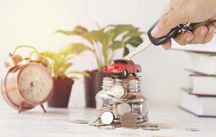 chiave della stretta della mano con il concetto di auto e denaro nell'acquisto di vendita di prestiti e assicurazione sui veicoli foto