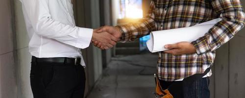 l'imprenditore edile stringe la mano all'ingegnere o al caposquadra dopo una negoziazione riuscita e un nuovo lavoro di ristrutturazione foto