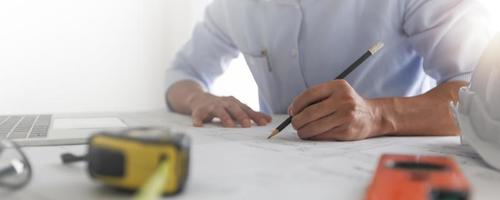 stretta di mano dell'ingegnere disegnare e progetto sul progetto sul tavolo architetto che lavora e crea in ufficio foto