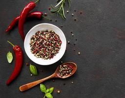 semi di peperoncino rosso piccante e baccelli su sfondo scuro vista dall'alto foto