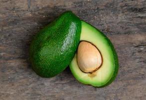 avocado fresco tagliato a metà sul fondo della tavola di legno foto