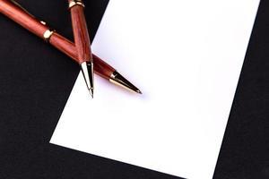 penna di lusso e portamine in legno e oro con un foglio di carta bianco foto