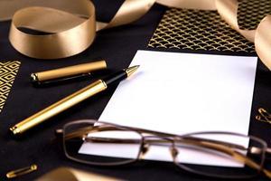 graffette e cancelleria nastro penna d'oro su sfondo nero con un foglio di carta bianco con spazio di copia foto