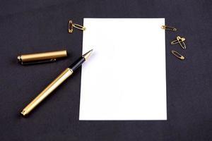 penna d'oro, nastro, graffette e articoli di cancelleria su uno sfondo nero con un foglio di carta bianco con spazio di copia foto