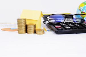 concetto di ipoteche con pila di monete e casa di carta gialla e occhiali da vista e calcolatrice sul documento grafico aziendale foto