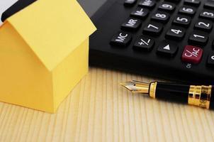 concetto di mutui ipotecari con close up penna stilografica e calcolatrice e casa di carta gialla sul fondo della tavola in legno foto