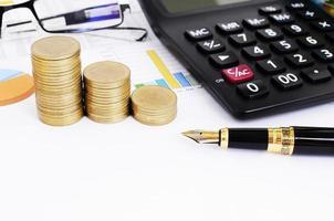 concetto di prestiti commerciali e finanziari con penna stilografica e monete pila e calcolatrice occhiali da vista sul documento grafico foto