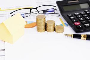 concetto di prestiti ipotecari con penna stilografica e pila di monete e tubo giallo di carta e occhiali da vista foto
