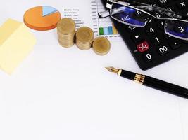 concetto di mutui ipotecari con carta gialla e funtain penna e monete e calcolatrice e occhiali da vista foto
