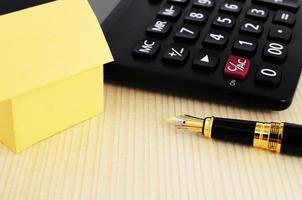 Close up di penna stilografica e calcolatrice e casa di carta gialla sul fondo della tavola in legno foto