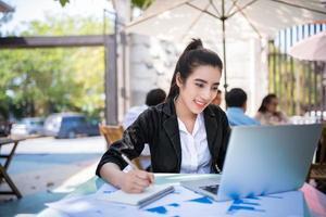 occupato giovane imprenditrice lavorando su una scrivania utilizzando un computer portatile in una caffetteria foto