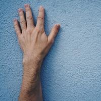 gesticolando con la mano sul muro foto