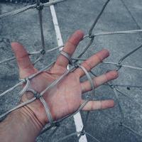 mano che tocca una rete di corda foto