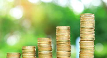 mucchio di monete impilate contro sfocato sfondo verde foto