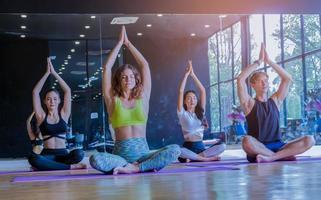 gruppo che esercita yoga in palestra allungando, concetto di esercizio sano foto
