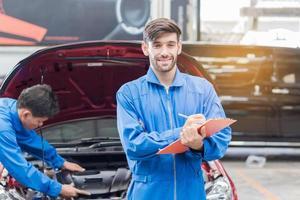 ritratto di un bel giovane tecnico in una veste blu che lavora in un centro di riparazione auto e verifica i dati tecnici foto